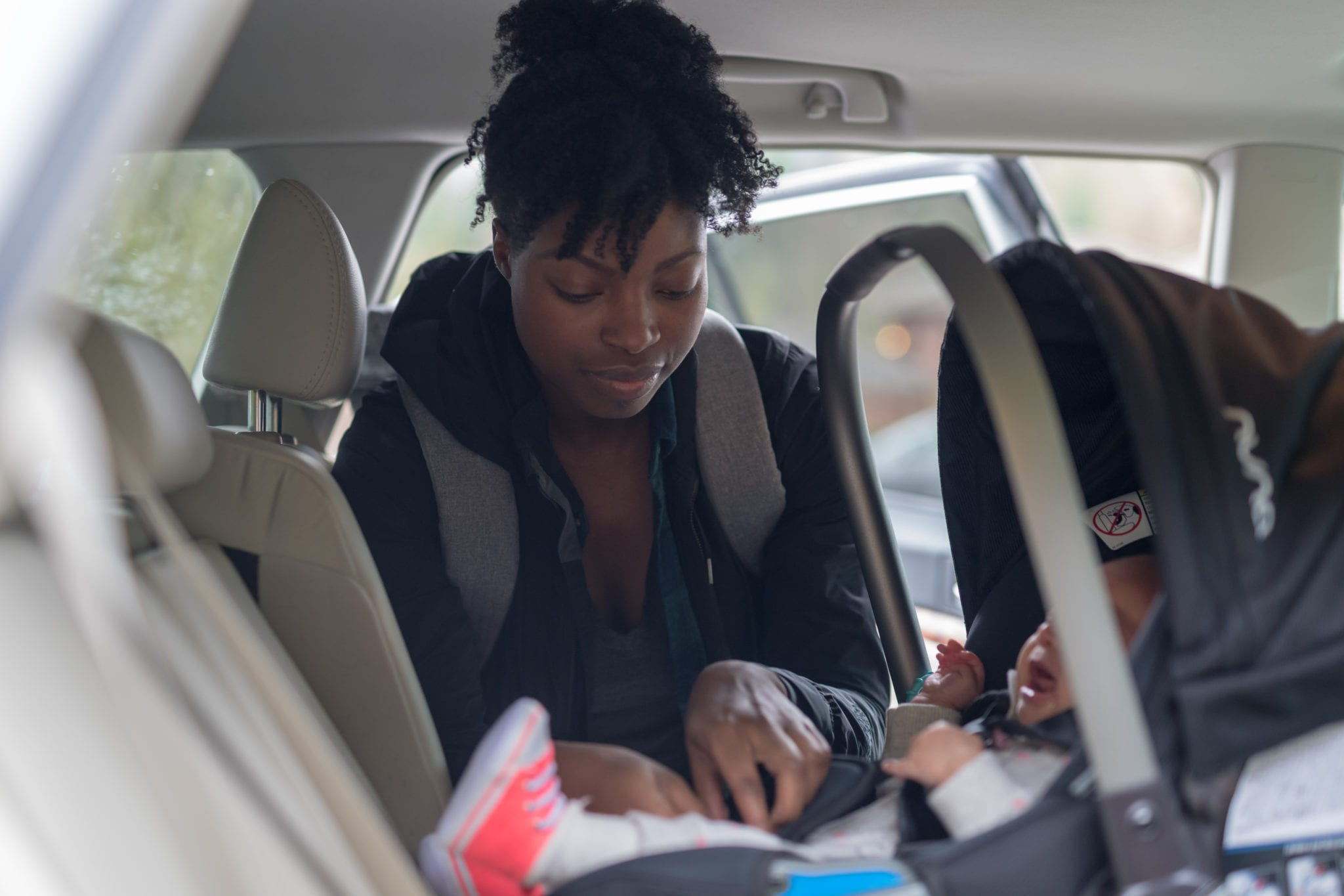 Mom puts her infant baby into the carseat